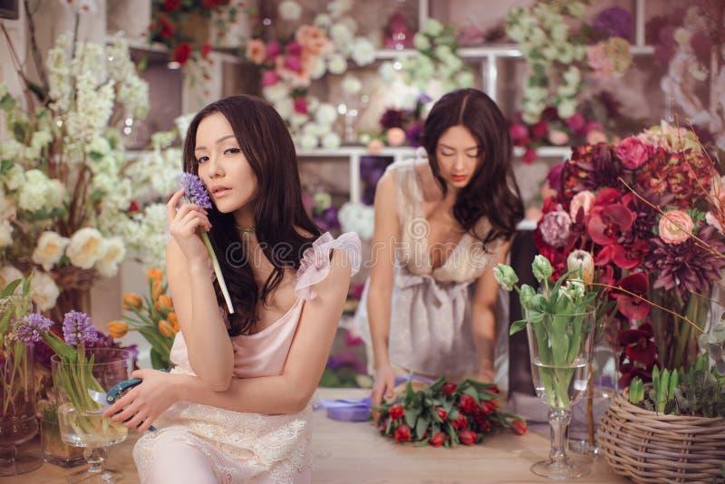El trabajo feliz de los floristas asiáticos hermosos de las mujeres en tienda de flor con mucha primavera florece imagen de archivo libre de regalías