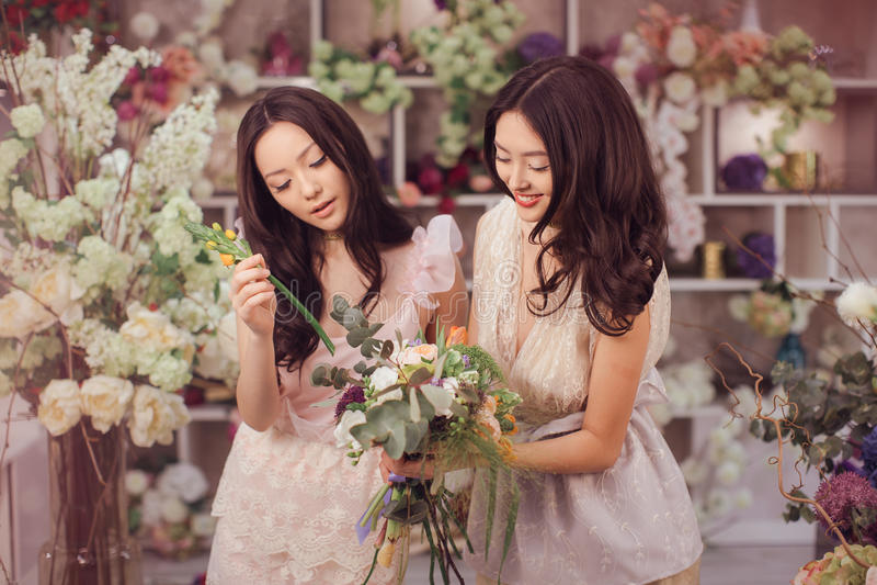 El trabajo feliz de los floristas asiáticos hermosos de las mujeres en tienda de flor con mucha primavera florece foto de archivo libre de regalías