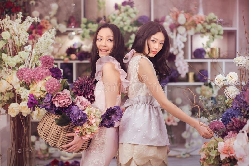 El trabajo feliz de los floristas asiáticos hermosos de las mujeres en tienda de flor con mucha primavera florece fotografía de archivo libre de regalías