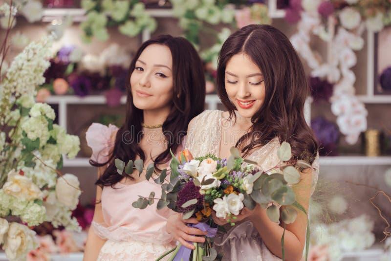 El trabajo feliz de los floristas asiáticos hermosos de las mujeres en tienda de flor con mucha primavera florece imágenes de archivo libres de regalías