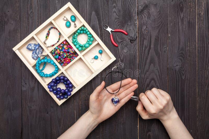 El trabajo hecho a mano en casa, la muchacha hace las manos de la joyería en la tabla fotografía de archivo libre de regalías