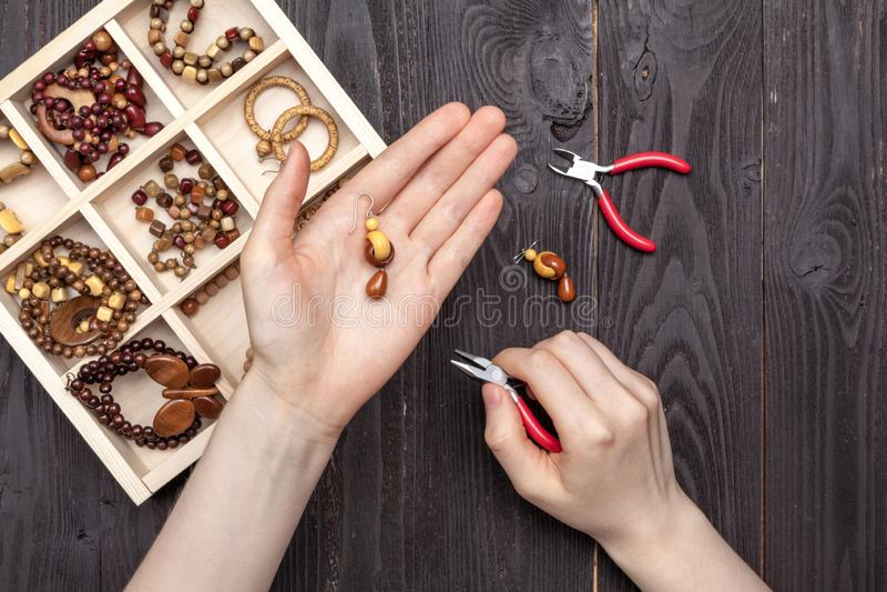 El trabajo hecho a mano en casa, la muchacha hace las manos de la joyería en la tabla foto de archivo