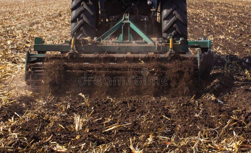 El tractor azul ara el campo y quita los restos del maíz previamente segado foto de archivo