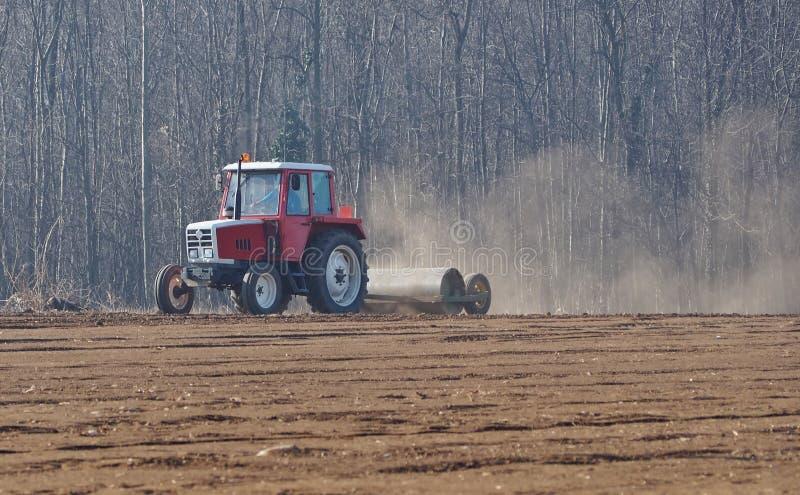 El tractor con un compresor remolcador del rodillo nivela la superficie del campo arado para preparar la siembra imagenes de archivo