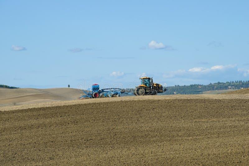 El tractor de correa eslabonada con el plantador funciona en el campo del día solar de septiembre imagenes de archivo