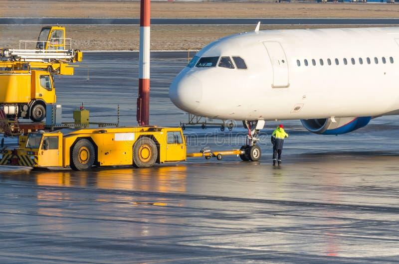 El tractor del pushback está remolcando los aviones a un estacionamiento, ordenar de la aviación imagenes de archivo