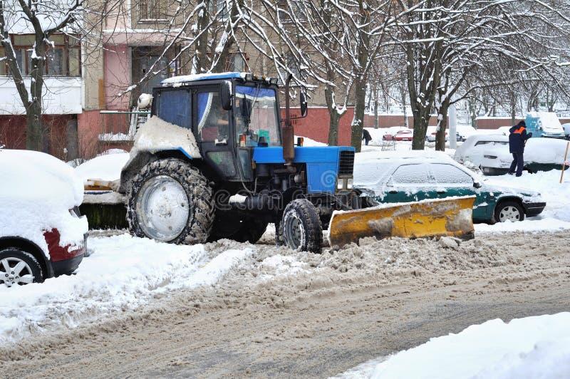 El tractor despeja nieve en patio imagenes de archivo