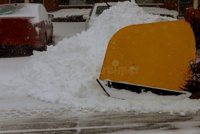El tractor quita nieve en la calle de la ciudad foto de archivo