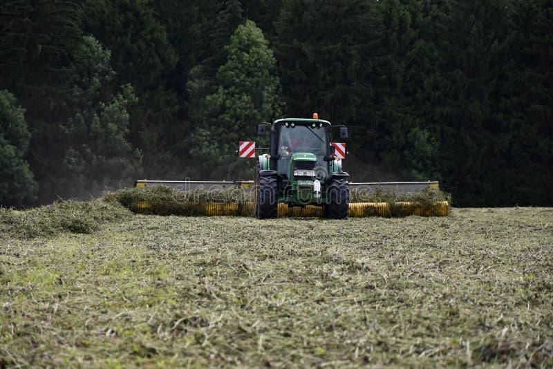 El tractor resume el trébol seco imagen de archivo