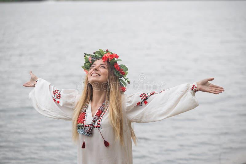 El tradisional que lleva de la mujer feliz joven se cierra y guirnalda imagen de archivo libre de regalías