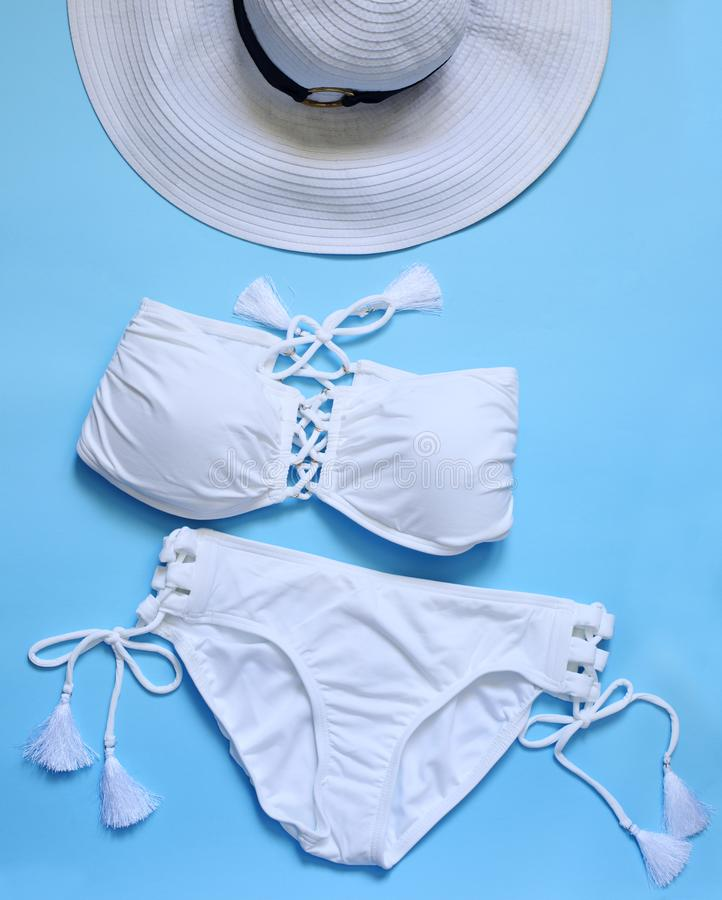 El traje de baño de las mujeres, sombrero blanco en fondo azul fotografía de archivo
