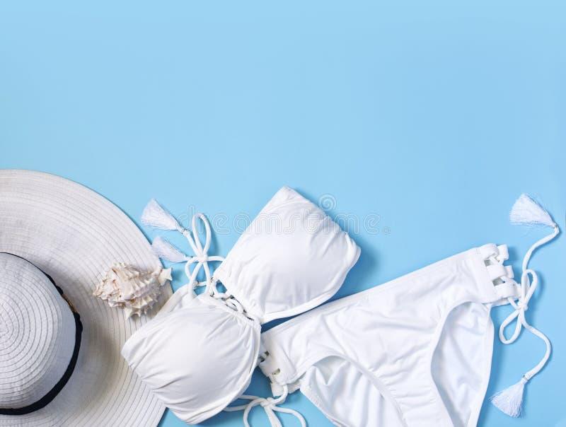 El traje de baño de las mujeres, sombrero blanco en fondo azul Composición puesta plana de la moda del verano foto de archivo libre de regalías