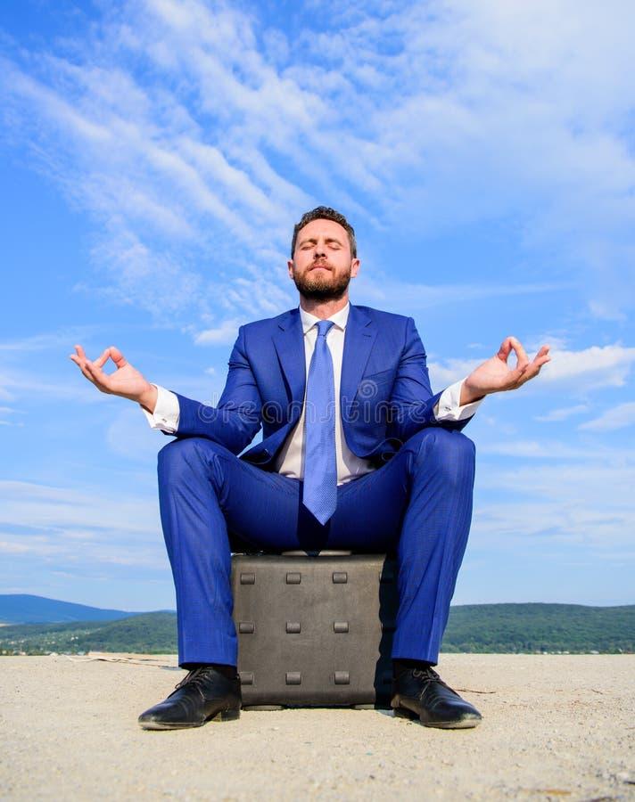 El traje formal del hombre de negocios se sienta en la cartera y meditar al aire libre Minuto del hallazgo del empresario a relaj fotos de archivo libres de regalías