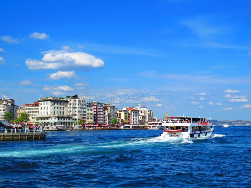 El transbordador navega a lo largo de las nuevas casas en los bancos del Bosphorus fotografía de archivo