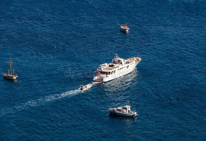 El transbordador pasa los barcos de pesca amarrados en el mar tirreno cerca de Positano Italia foto de archivo
