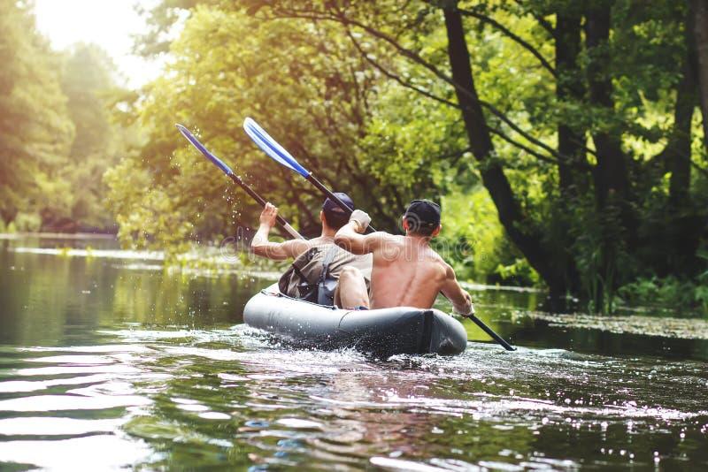 El transportar en balsa en el río en un kajak en la estación de verano Ocio Dos personas en la fila del barco con los remos foto de archivo