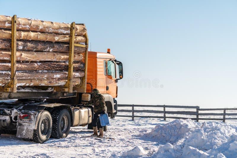 El transporte del camión de los árboles parqueado en nieve, con el conductor añade el combustible en invierno foto de archivo