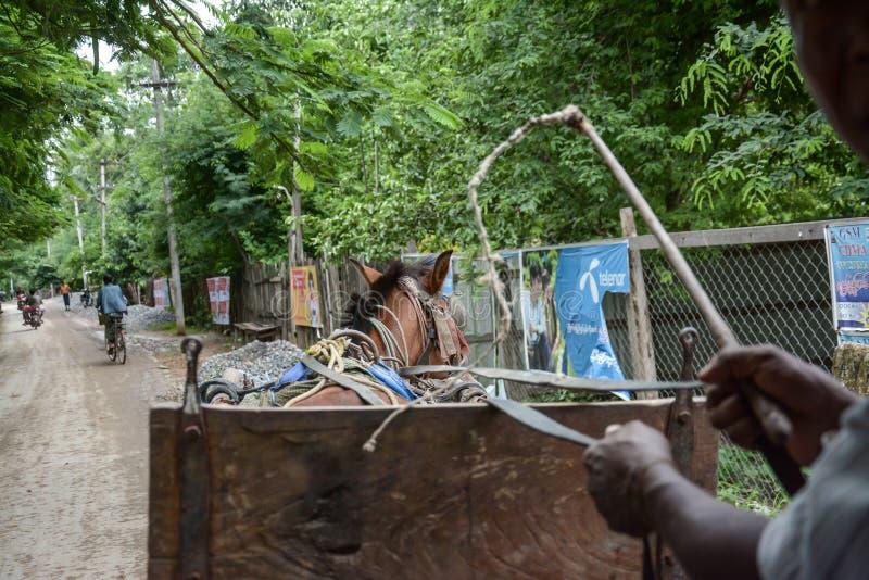 El transporte no identificado de personas y llevar suministra los funcionamientos locales del camino adelante a un pueblo en Inwa foto de archivo libre de regalías