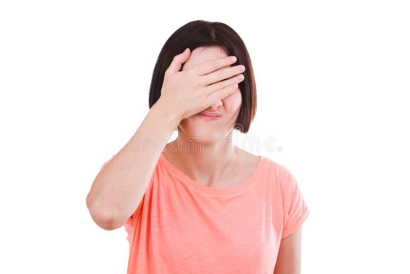 El trastorno de la muchacha cubrió su cara con su mano en un fondo aislado blanco imágenes de archivo libres de regalías
