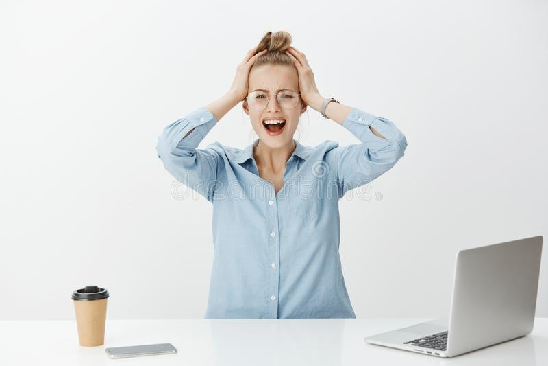 El trastorno devestated al compañero de trabajo femenino atractivo en oficina, sentarse y cabeza conmovedora mientras que gritaba imágenes de archivo libres de regalías