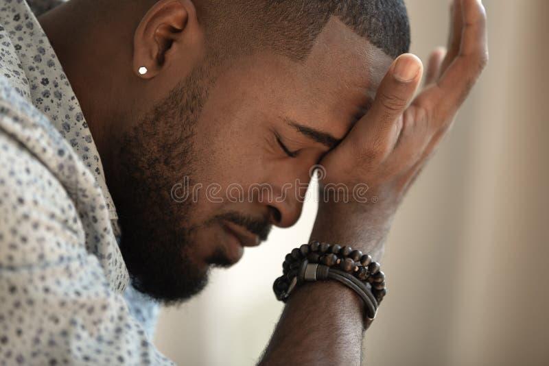 El trastorno subrayó al hombre afroamericano joven que hacía frente a dolor de cabeza fuerte foto de archivo