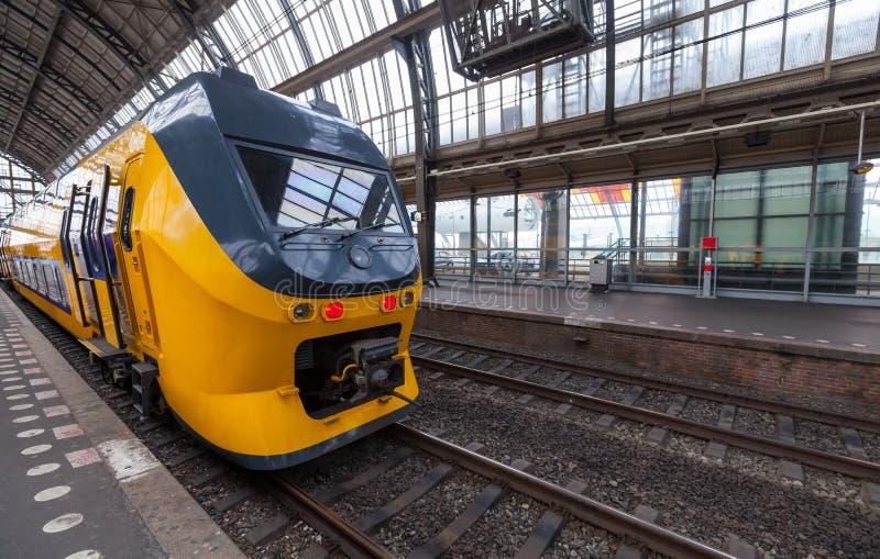 El tren amarillo se coloca en la estación de Amsterdam imagenes de archivo