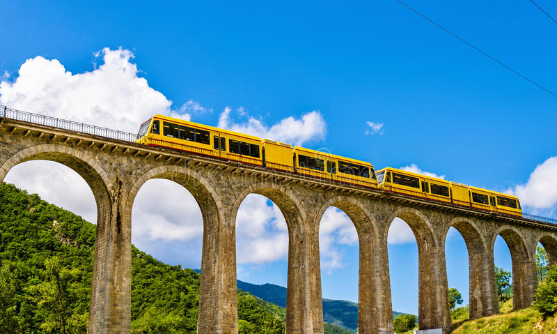 El tren amarillo (tren Jaune) en el puente de Sejourne fotografía de archivo