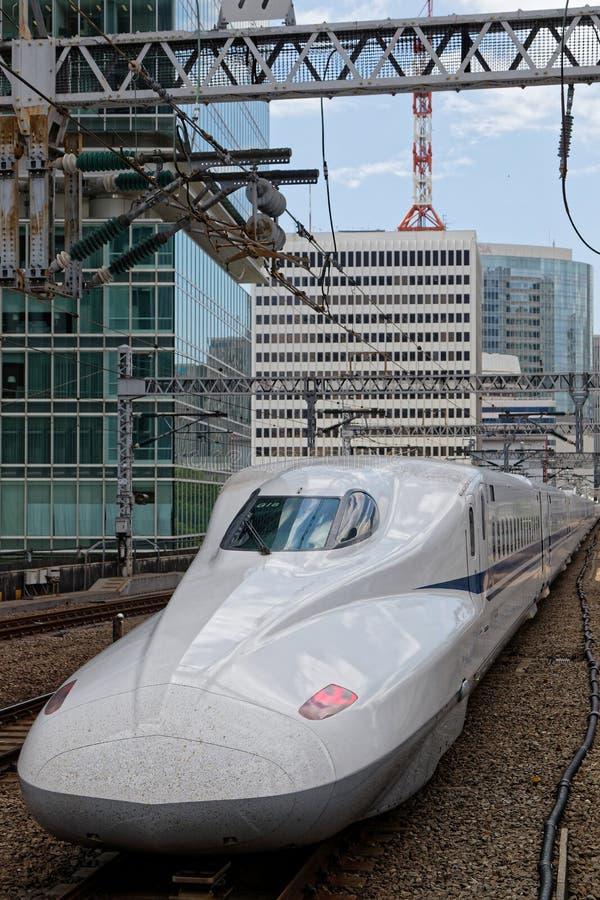 El tren blanco incorpora la estación con el edificio en el fondo fotografía de archivo