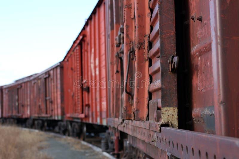 El tren de carga oxidado viejo se coloca en los carriles foto de archivo