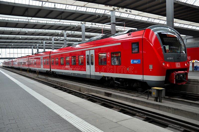 El tren de cercanías rojo parqueó en la estación de Munich, Alemania imagenes de archivo