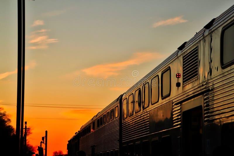 El tren de Metra viaja en la puesta del sol en el final de un último día de invierno imagen de archivo libre de regalías