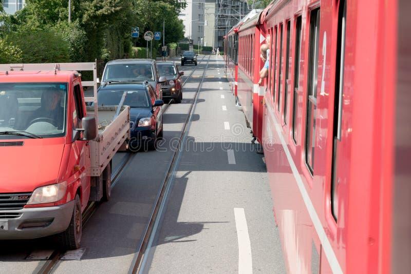 El tren ferroviario rojo de Rhatian para tráfico mientras que conduce a lo largo de los caminos de Chur céntrico fotografía de archivo libre de regalías