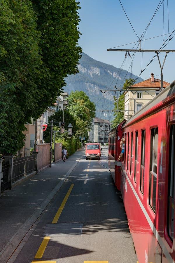El tren ferroviario rojo de Rhatian para tráfico mientras que conduce a lo largo de los caminos de Chur céntrico imagen de archivo