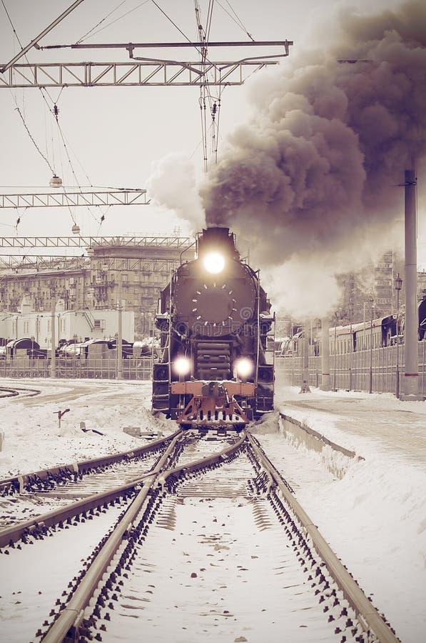 El tren retro del vapor sale del ferrocarril en la puesta del sol foto de archivo