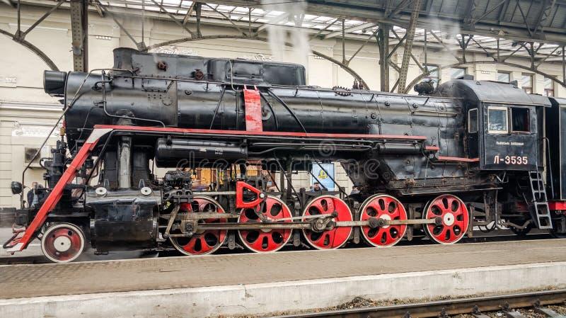 El tren retro del viejo negro soviético del vintage con una estrella roja en el ferrocarril en Lviv produce el vapor de los tubos foto de archivo libre de regalías