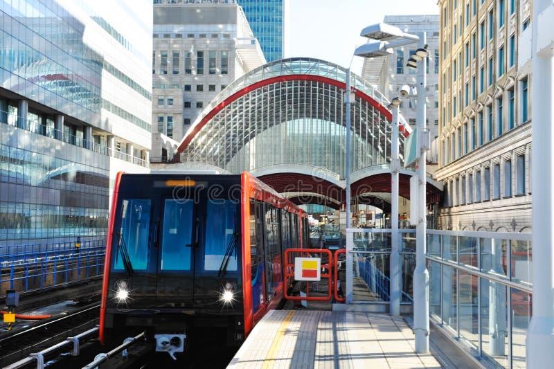 El tren se acerca a la estación de los docklands en Londres imagen de archivo