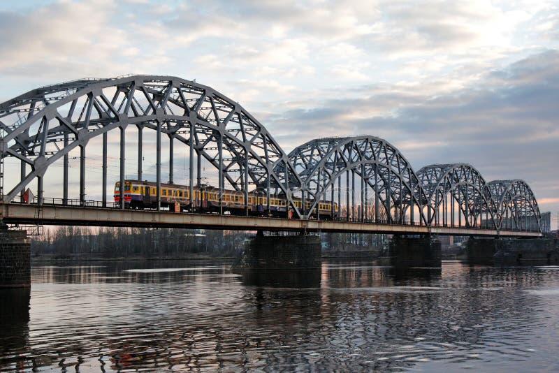 El tren viaja a lo largo del puente ferroviario a través del río del Daugava foto de archivo libre de regalías