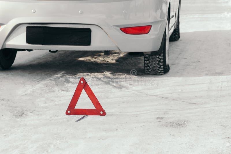 El triángulo amonestador reflexivo antes del vehículo, una situación de emergencia en el camino en invierno, pide ayuda Coche ana fotos de archivo libres de regalías