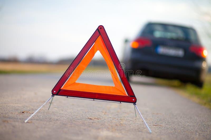 El triángulo de la avería se coloca en un coche quebrado fotos de archivo libres de regalías