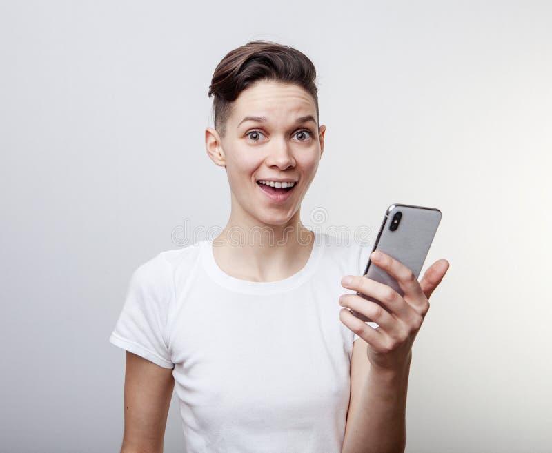 El triunfo o victoria de celebración, triunfo de la mujer milenaria divertida feliz, sosteniendo un teléfono Muchacha emocionada  imágenes de archivo libres de regalías