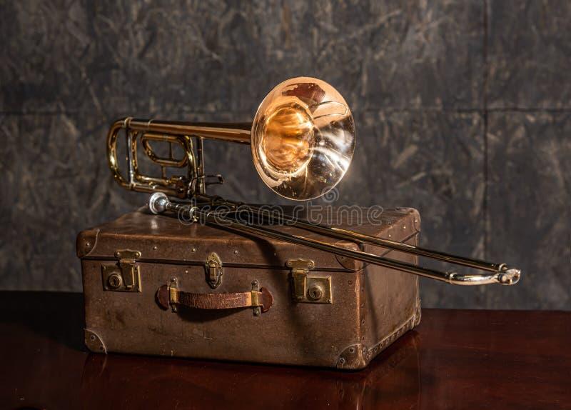 El trombón de instrumentos musicales yace en una vieja maleta fotografía de archivo libre de regalías