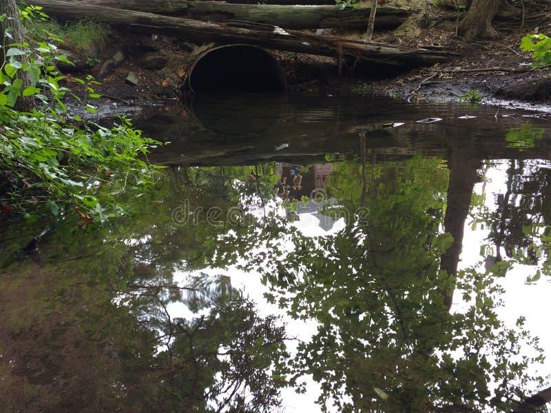 El tubo de agua saca el agua de la contaminación del alcantarillado de la ciudad fotografía de archivo libre de regalías