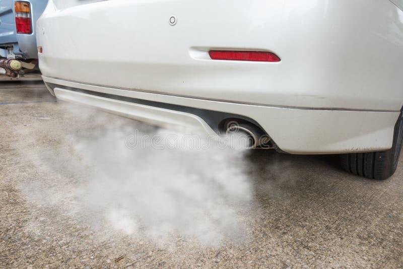 El tubo de escape del coche sale fuertemente del humo, concepto de la contaminación atmosférica imagenes de archivo