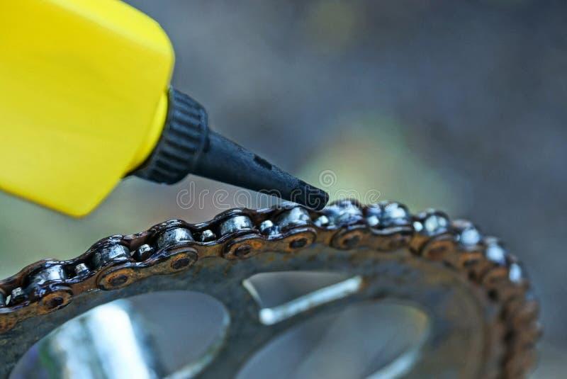 El tubo plástico engrasa una cadena oxidada en una bicicleta fotos de archivo
