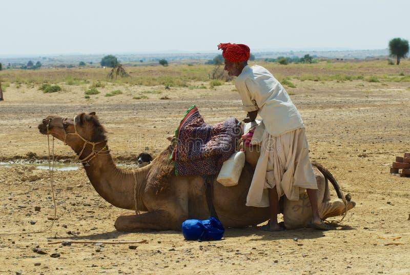 El turbante que lleva del hombre y el vestido tradicional consigue su camello listo para un paseo del safari en el desierto cerca foto de archivo libre de regalías