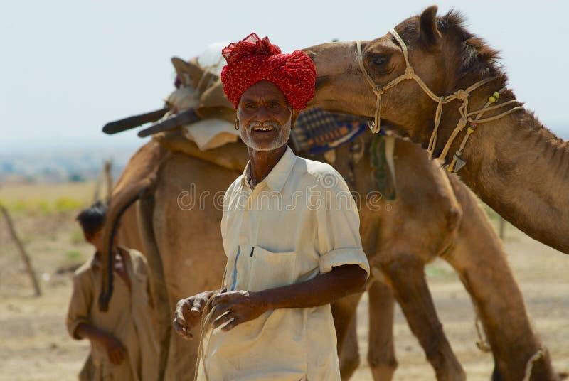 El turbante que lleva del hombre y el vestido tradicional consigue su camello listo para un paseo del safari en el desierto cerca foto de archivo