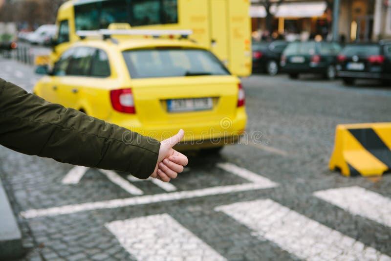 El turista aumentó su finger para arriba e intentando coger un taxi fotografía de archivo libre de regalías
