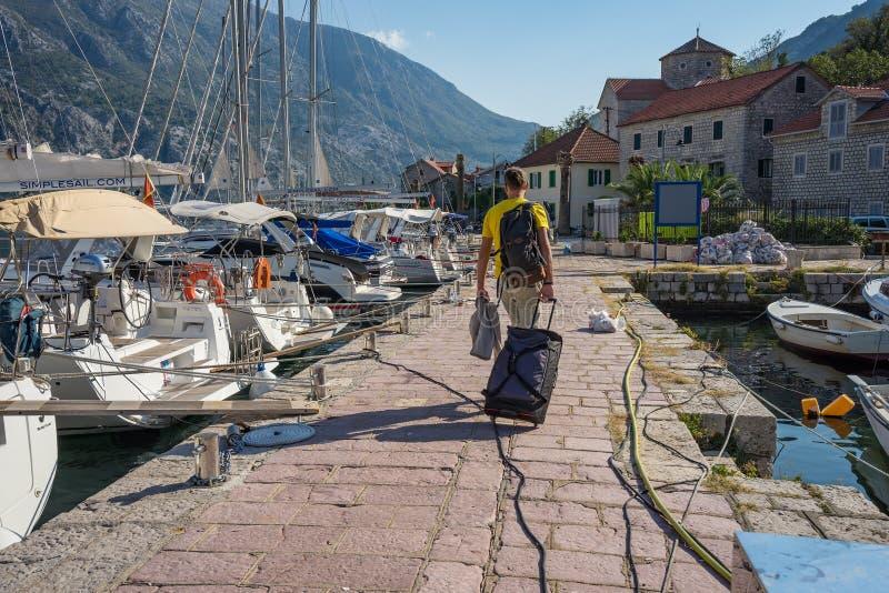 El turista con una maleta y una mochila camina a lo largo de los yates y de las motoras amarrados en el embarcadero imagenes de archivo