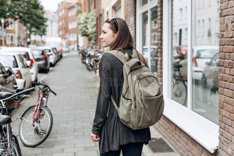El turista con una mochila está buscando el alojamiento en línea reservado en una ciudad desconocida fotos de archivo