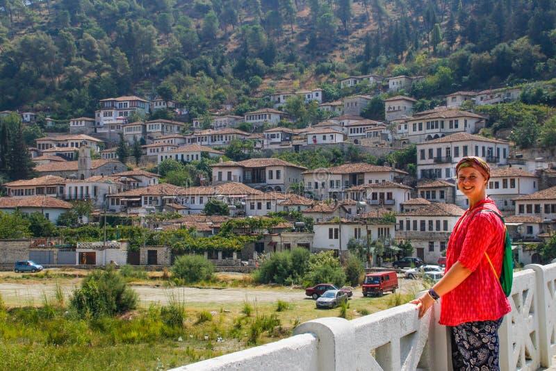 El turista de la chica joven en una blusa rosada se coloca en un puente sobre el río Lumi i Osumit en la ciudad de Berat foto de archivo libre de regalías